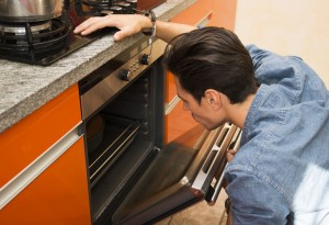 Man watching something cook in the oven